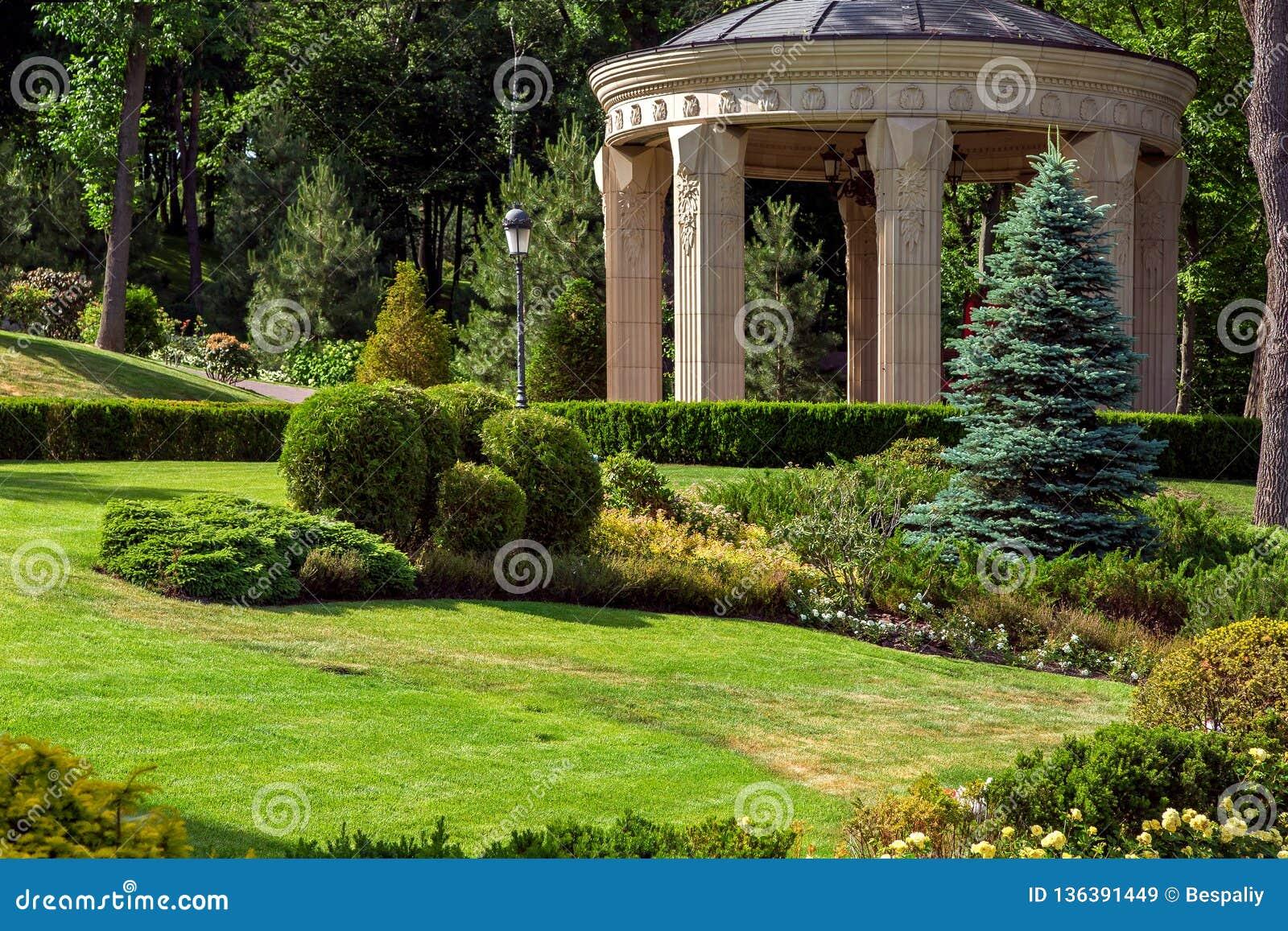 Stenaxeln med kolonner i parkerar med landskapdesign
