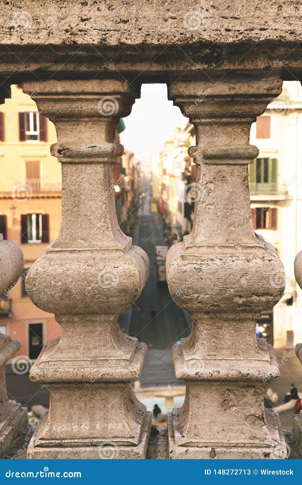 Stenbaluster med den suddiga gatan i bakgrunden
