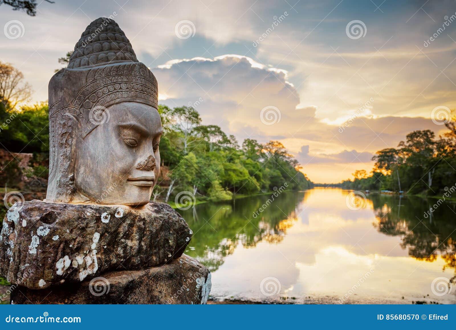 Stenframsida Asura och solnedgång över vallgraven angkorcambodia thom
