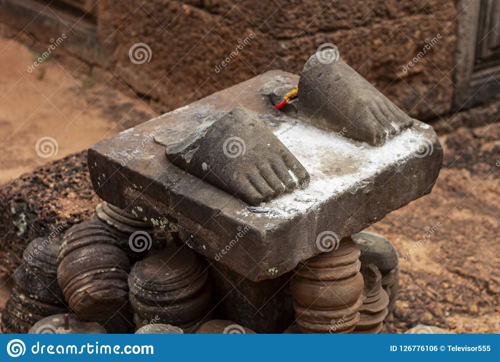 Stenstatyfoten fördärvar i det Angkor Wat tempelkomplexet, Cambodja Bruten statyfot på sockel