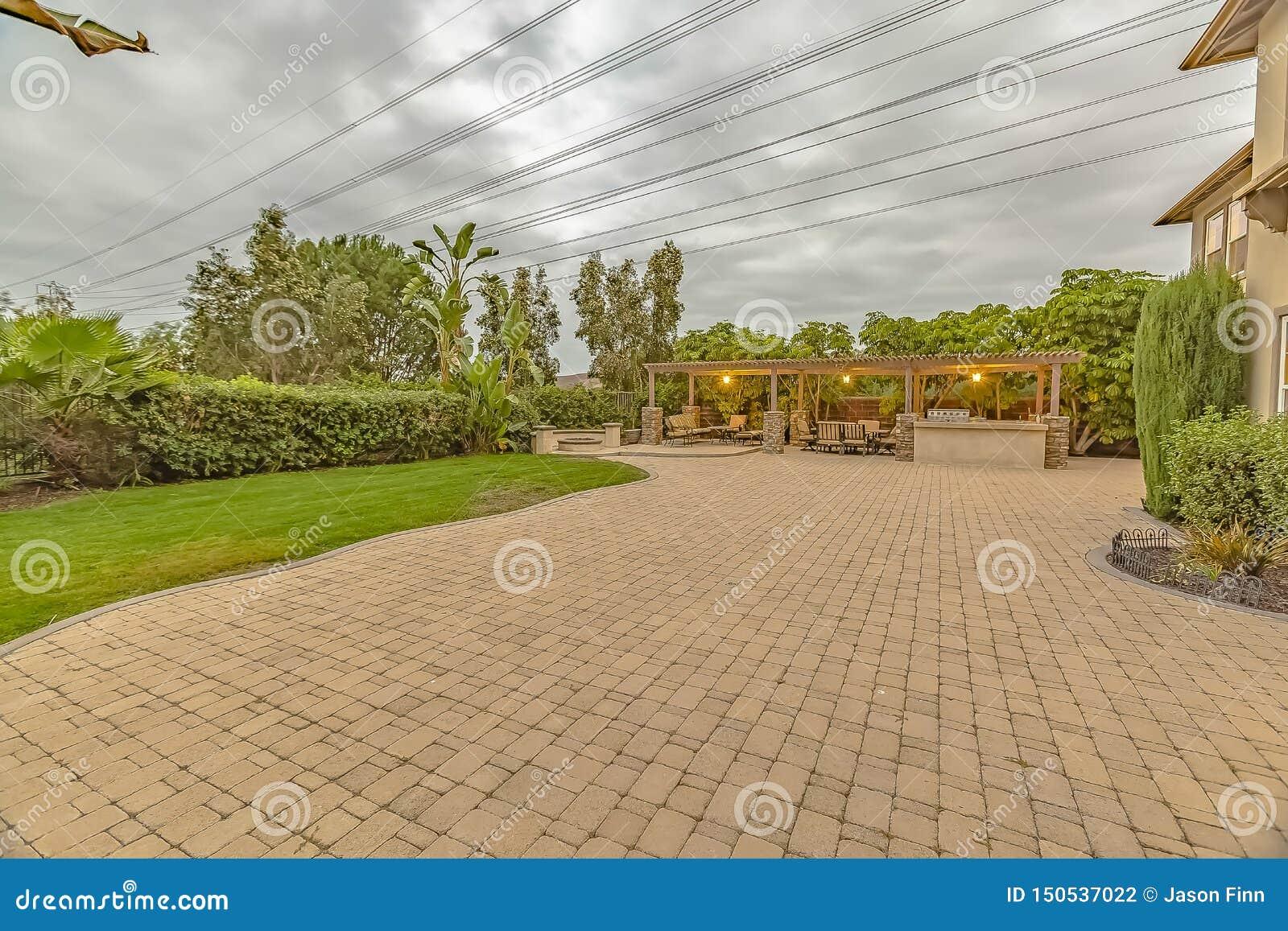 Stentegelstenkörbana och uteplats med brandgropen och äta middag område under en paviljong