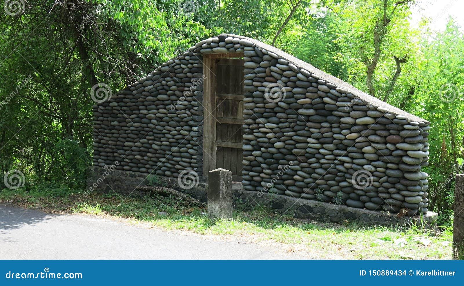 Stenvägg med den stängda gamla trädörren vid vägen En vägg av stenar i djungeln Stenar från floden att vattnet arbetade in