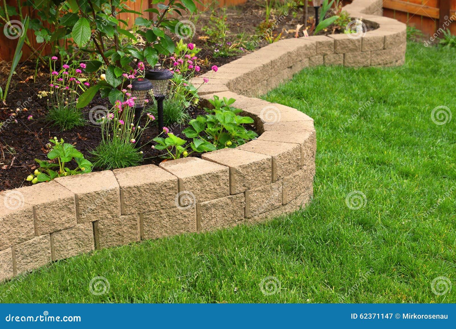 Stenvägg med perfekt gräs som landskap i trädgård med konstgjort gräs