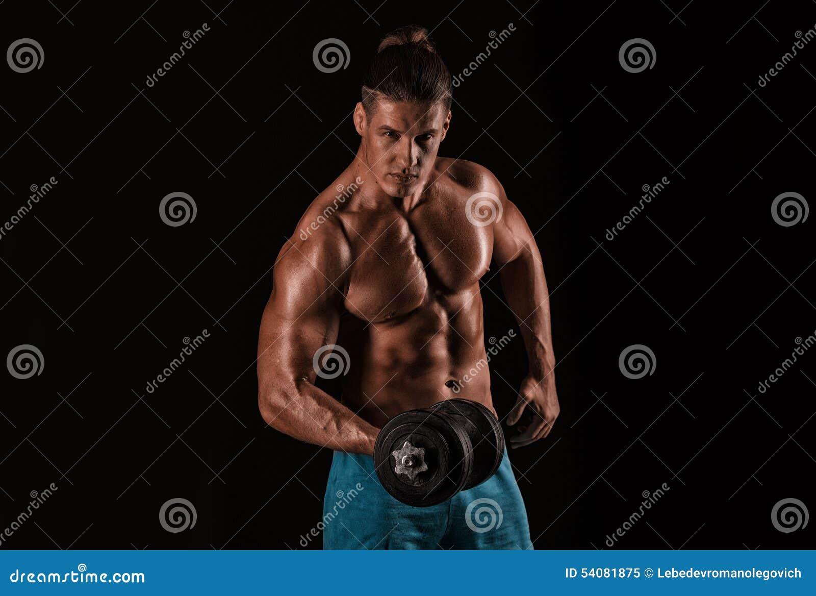 Sterke atletische mens met het perfecte lichaam stellen met domoren