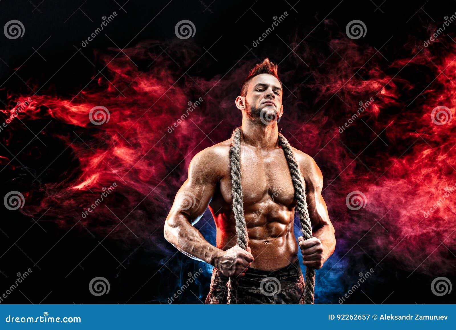 Sterke atletische mens met naakt lichaam in militaire broek en kabel op halszwarte