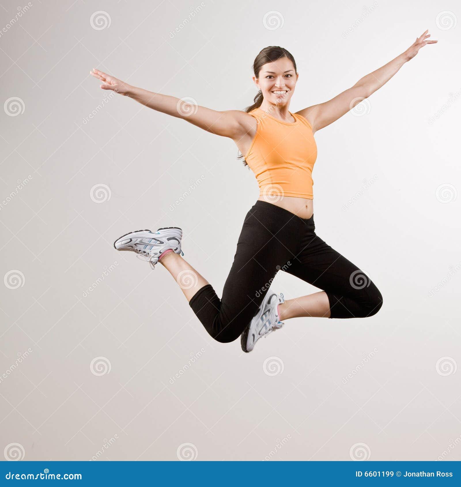 Sterke atletische vrouw die in mid-air springt