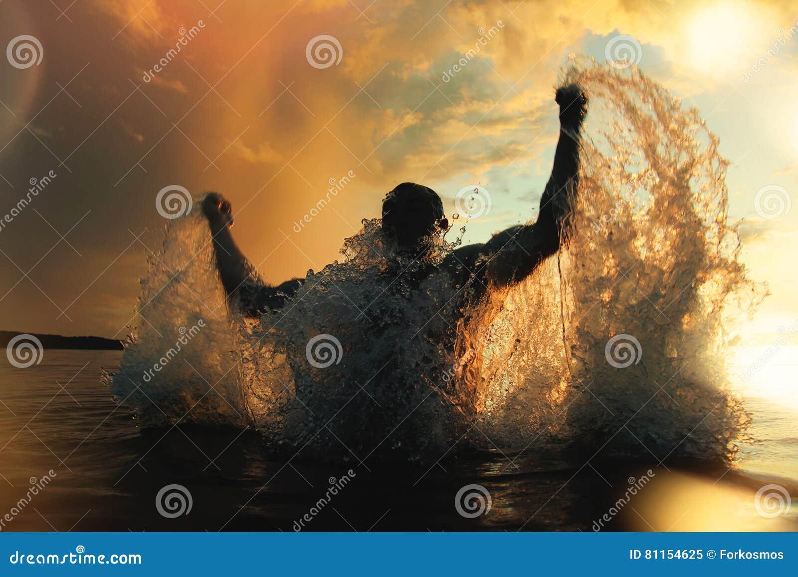 Sterke en atletische mensensprongen uit het water bij zonsondergang