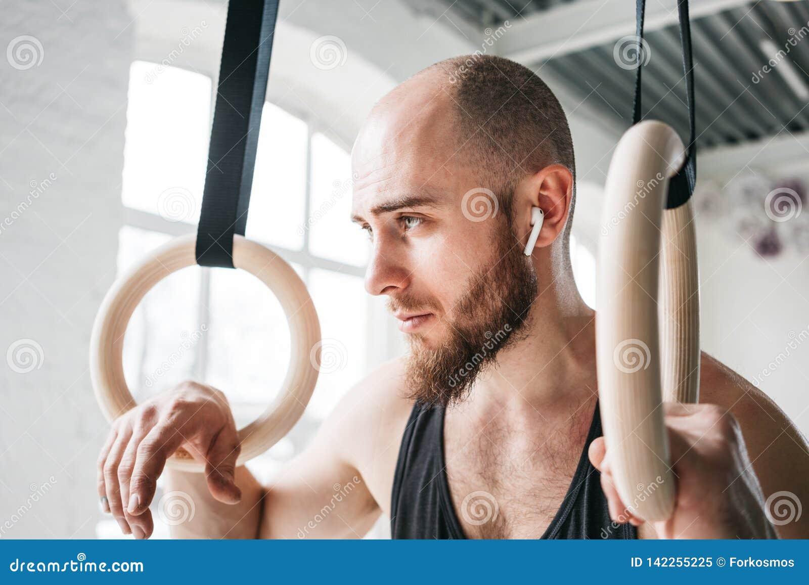 Sterke gebaarde atleet met de draadloze crosstraining ringen van de hoofdtelefoonholding bij crossfitzaal