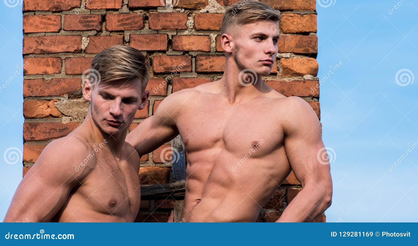 Sterkte en gunst Bodybuilder van de mensen toont de spieratleet spieren Bakstenen muur van de het torsotribune van de mensen de s