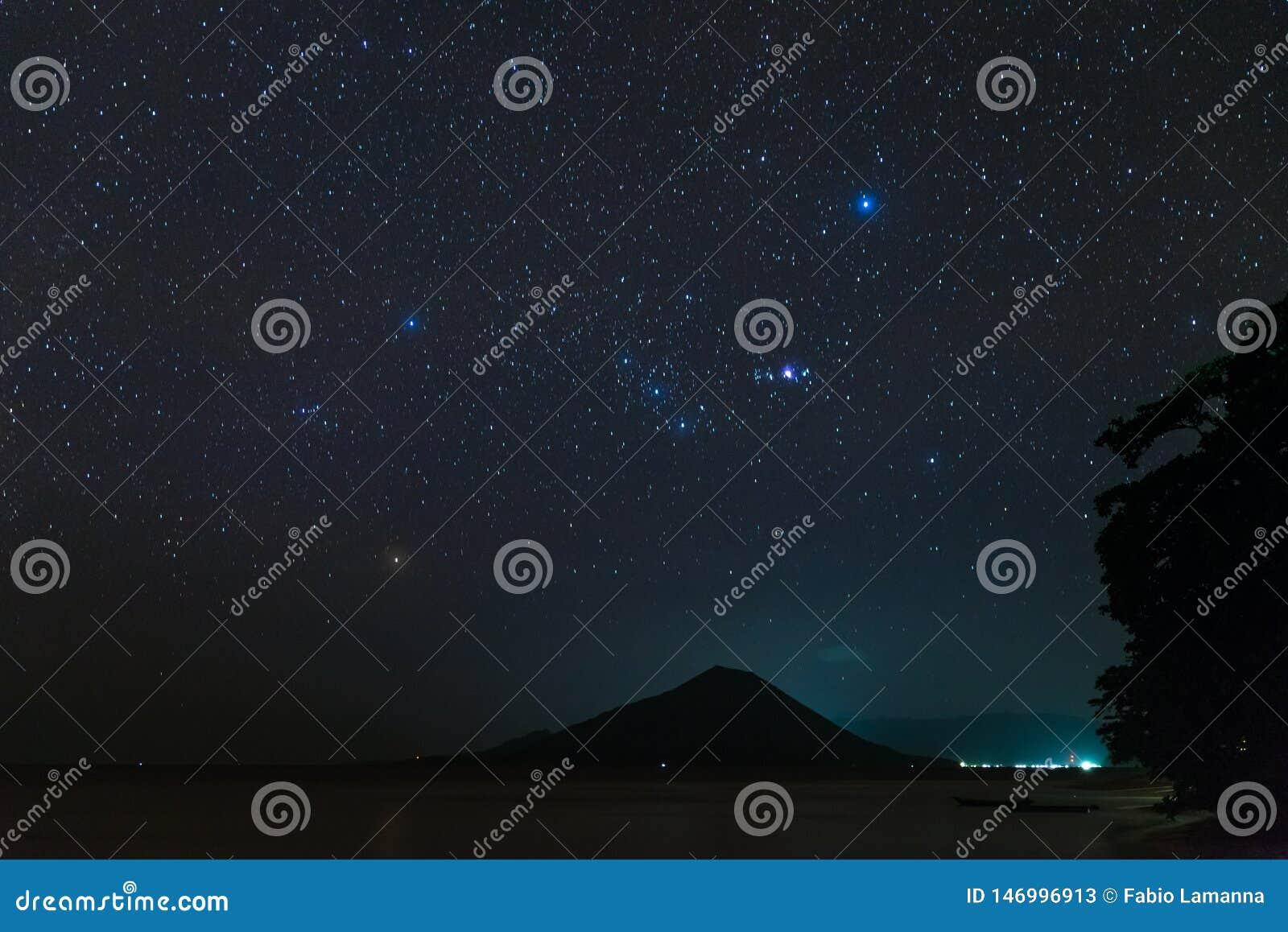 Sterrige de hemelsterren van de Orionconstellatie over het vulkanische eiland die van Gunung Api in tropische nacht Indonesië Ban