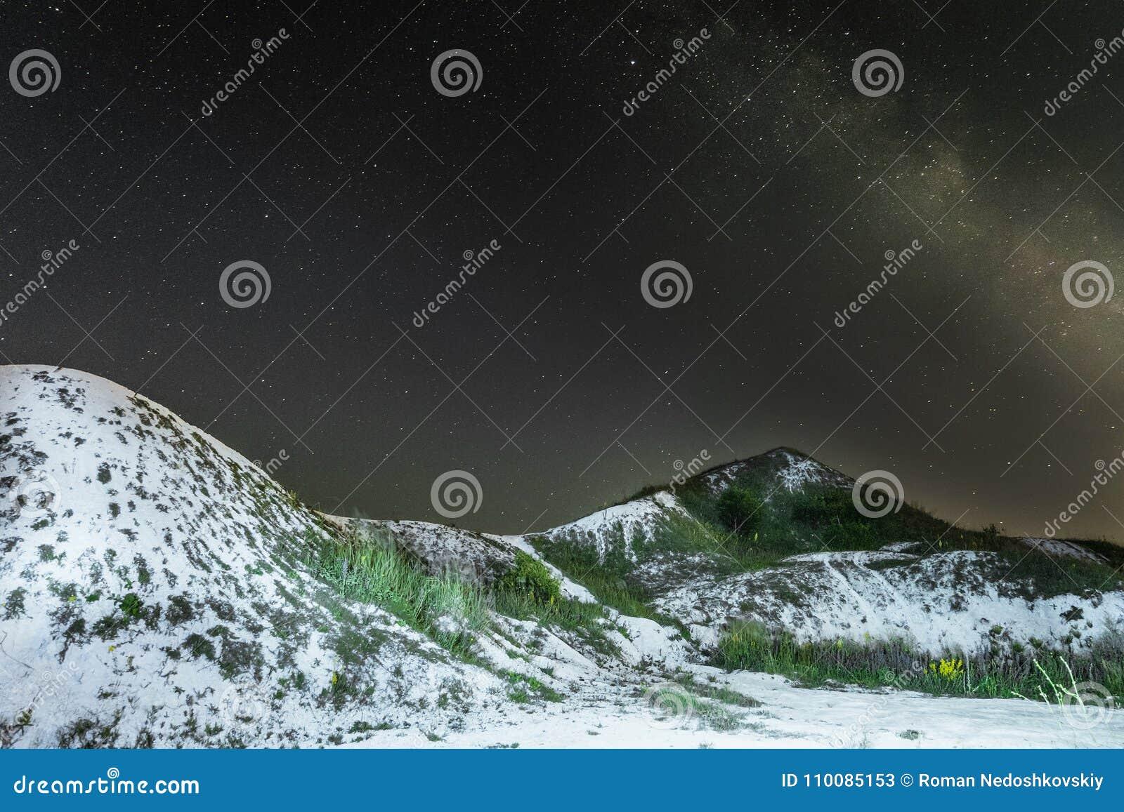 Sterrige nachthemel met melkachtige manier over de witte krijtachtige heuvels Nacht natuurlijk landschap met krijtranden