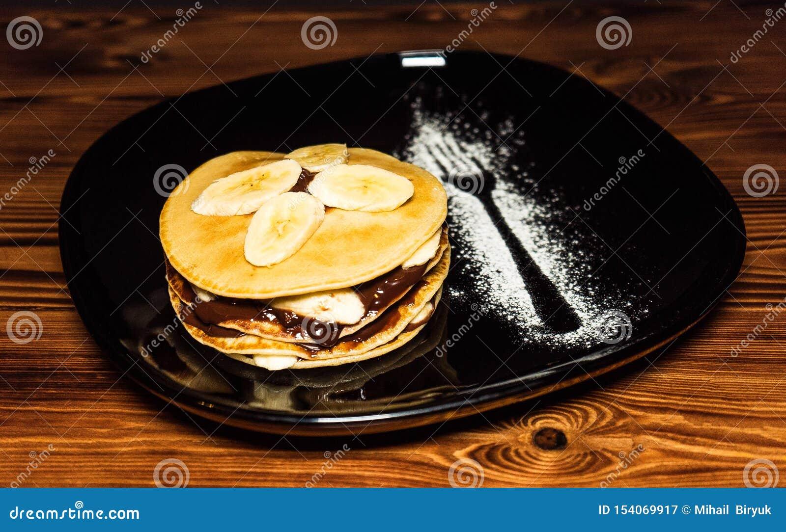 Sterta bliny z bananów plasterkami i czekoladowy syrop na talerzu