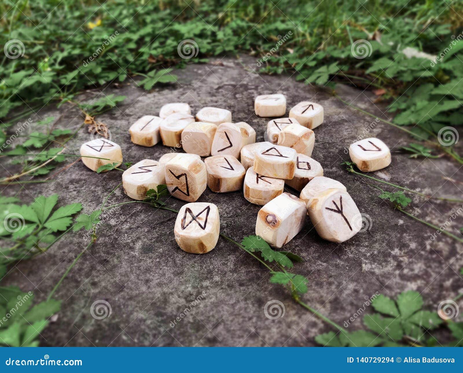 Sterta drewniani runes przy lasowymi Drewnianymi runes kłama na rockowym tle w zielonej trawie Runes cią od drewnianego