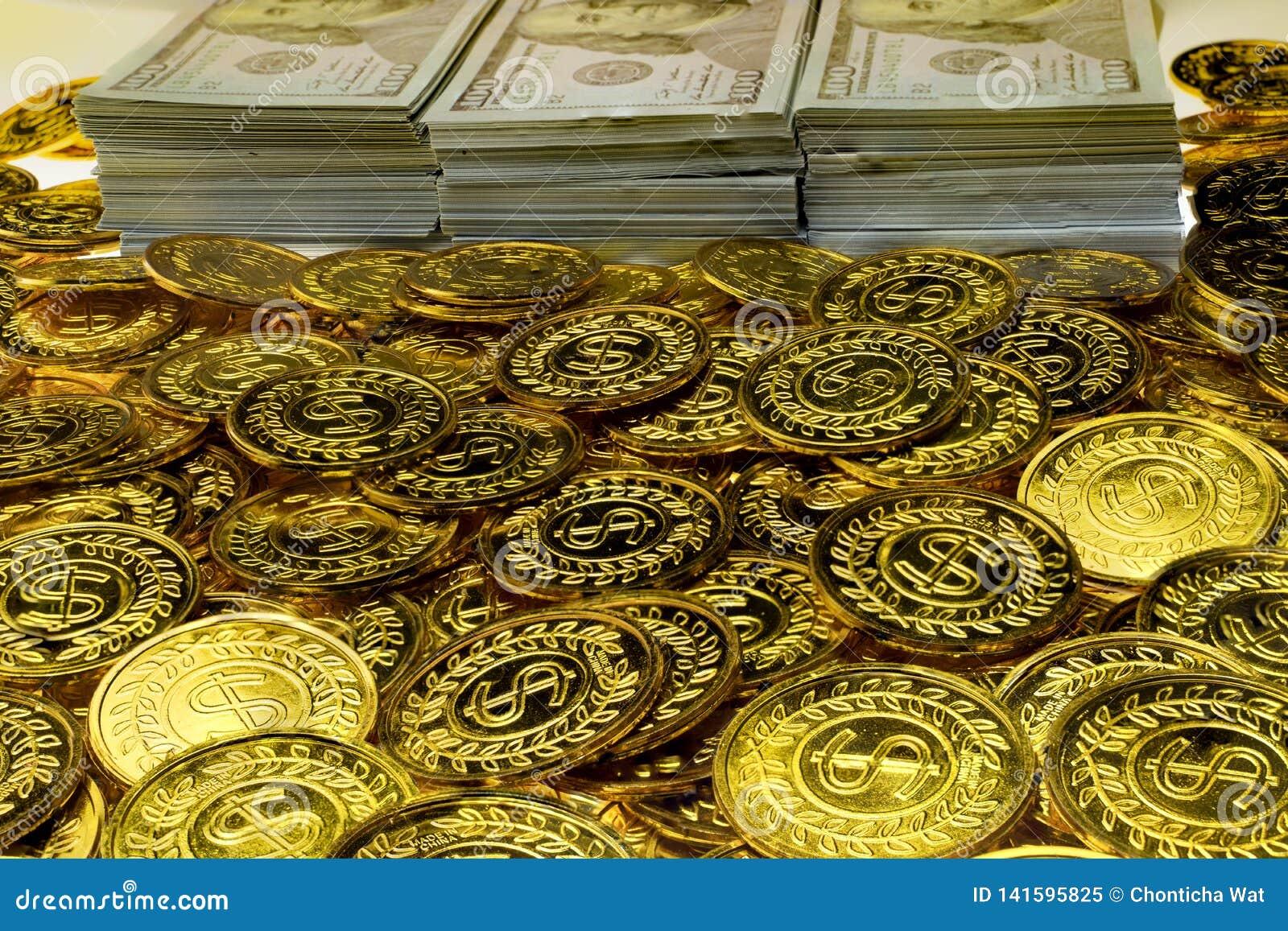 Sterta pliki 100 USA dolarów i złocistych monet banknoty