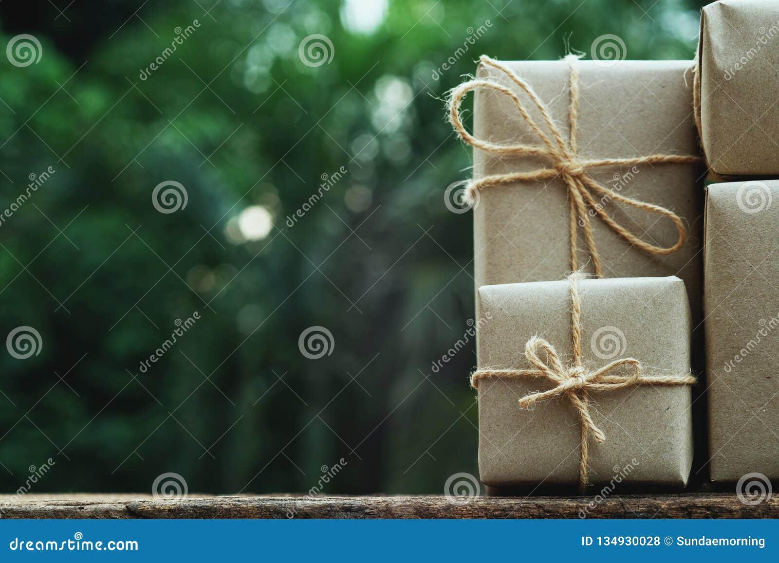 Sterta prostego eco prezenta pudełka pakunku życzliwy opakunek z brązu papierem w starym drewnianym stołowym tle, zieleni teraźni