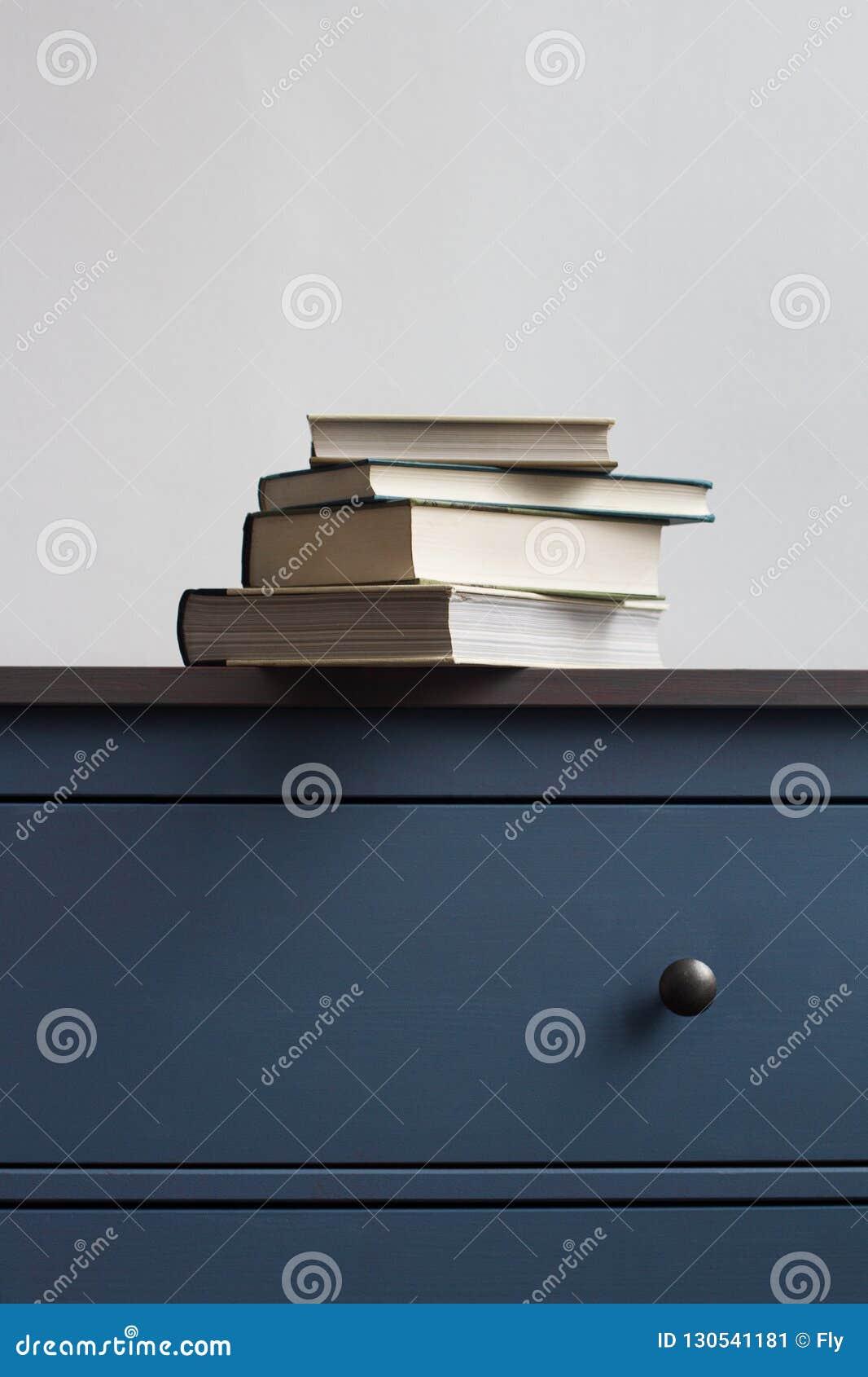 Sterta zamknięte książki na błękitnej klatce piersiowej kreślarzi