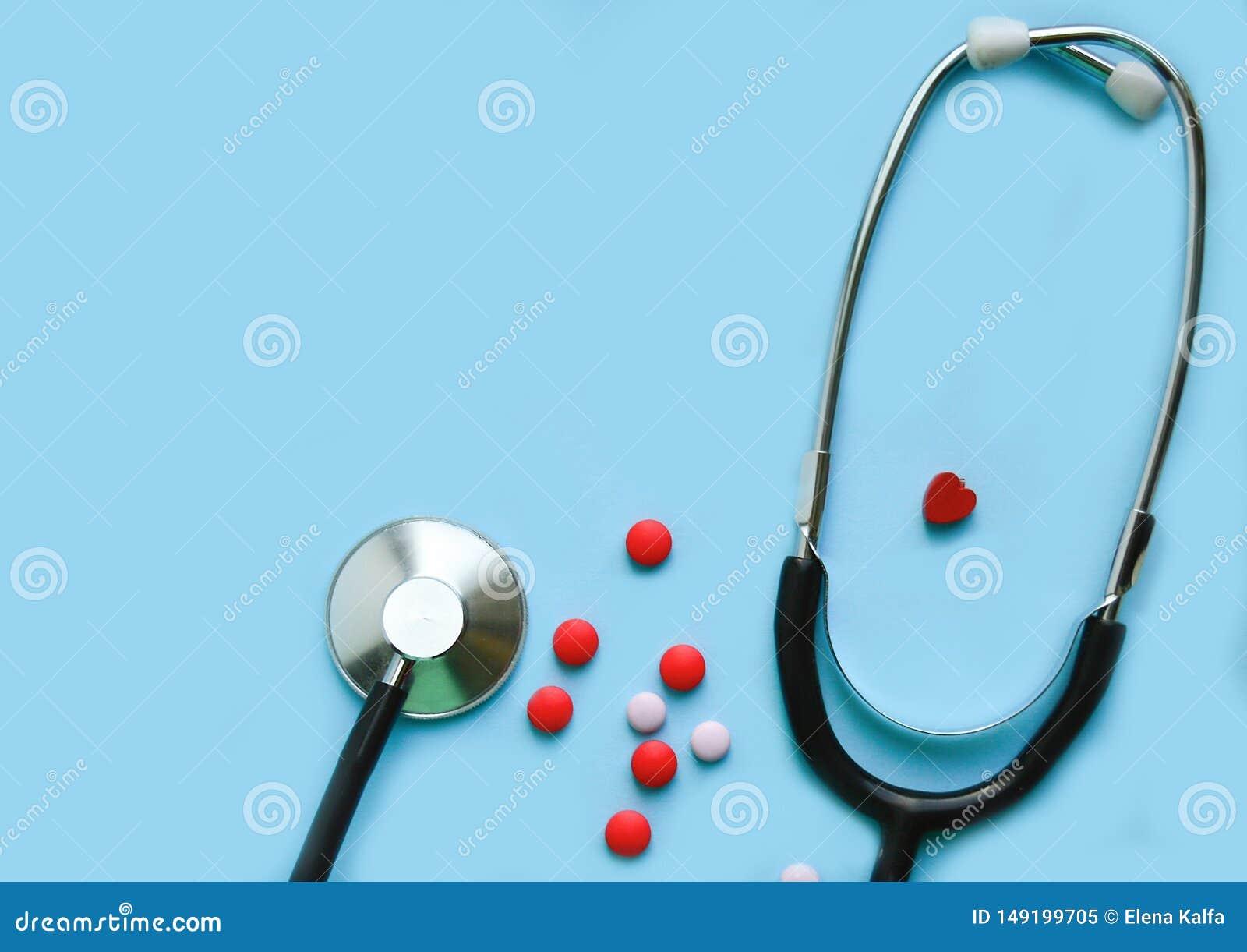 Stethoscoop op een blauwe achtergrond met pillen en een rood hart, beschikbare ruimte
