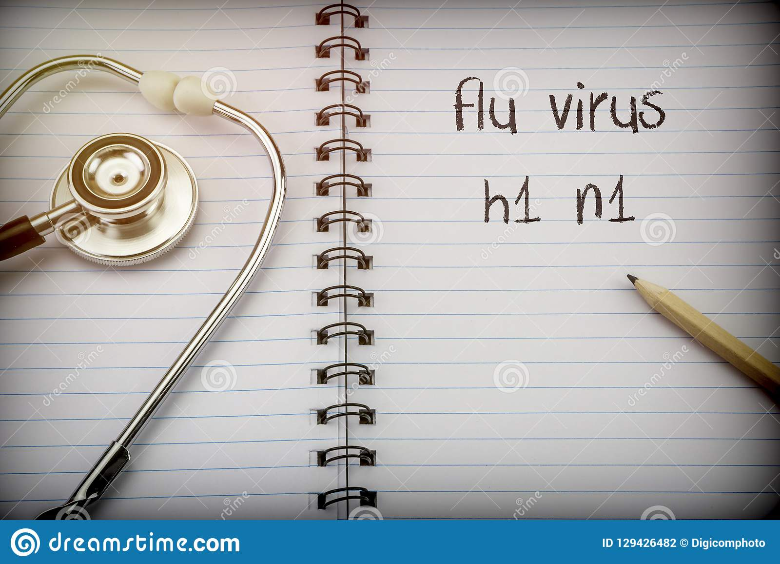 Stethoscope on notebook and pencil with flu virus h1 n1 words as