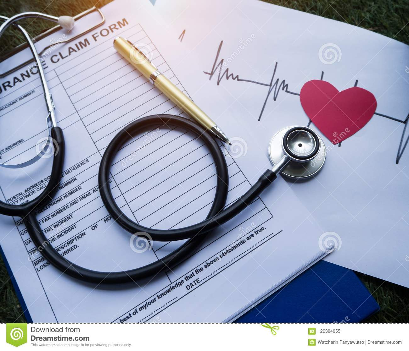 The Stethoscope put on the insurance claim form,beside cutted red heart paper and heart rate drawing ,on green grass ground floor