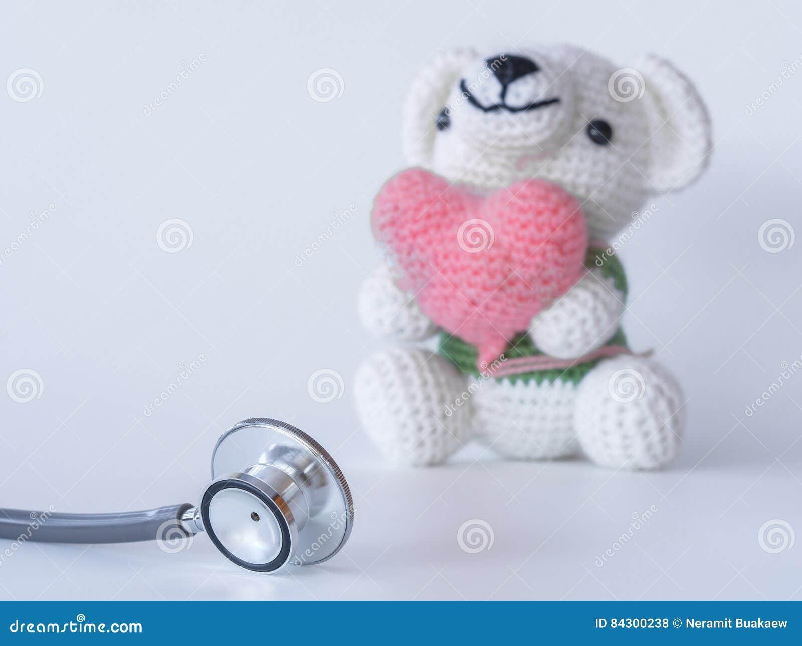 Stethoskop Und Teddybär, Die Ein Herz Auf Weißem Hintergrund Halten ...