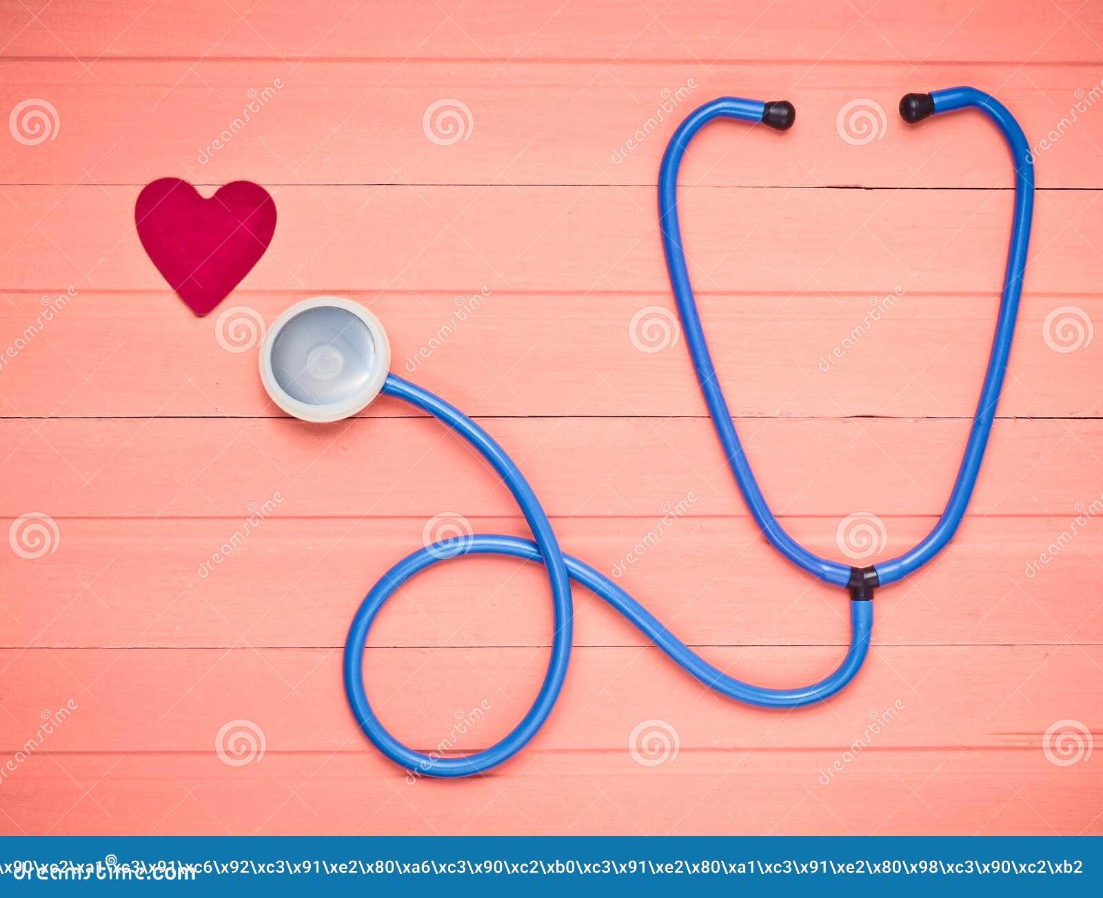 Stetoscopio e cuore sulla tavola di legno di rosa pastello Attrezzatura di cardiologia per la diagnostica delle malattie cardiova
