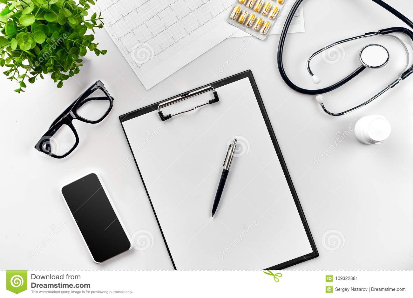 Stetoskop i kontoret av doktorer Bästa sikt av tabellen för skrivbord för doktors` s, tomt papper på skrivplattan med pennan kopi