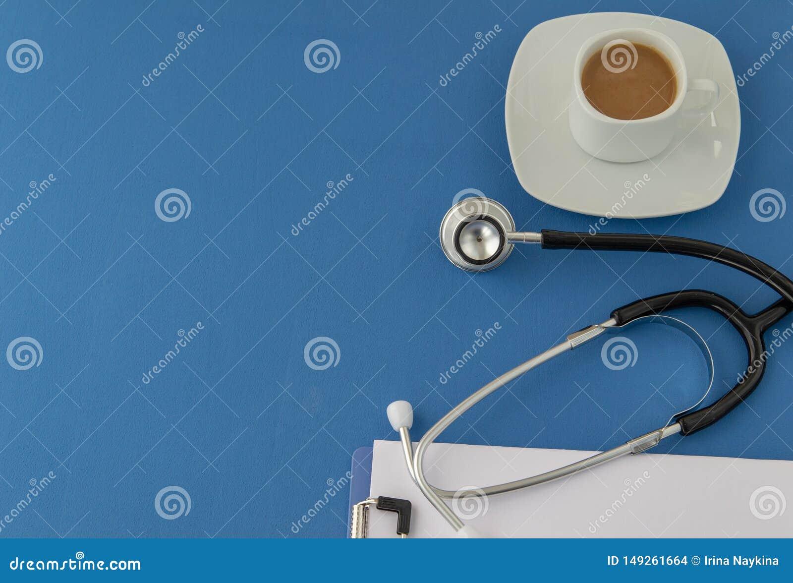 Stetoskop kopp kaffe på en blå bakgrund stetoskop f?r pengar f?r begreppsliesmedicin set