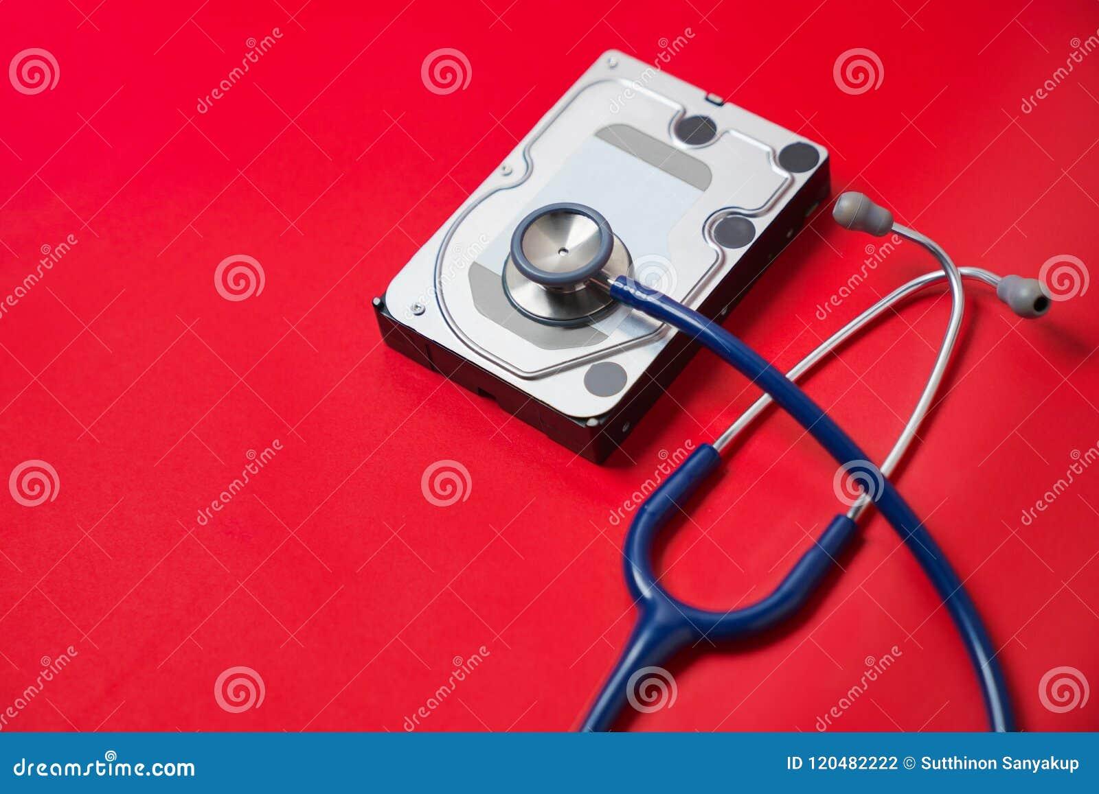 Stetoskop- och hårddiskdrev på röd bakgrund Diagnostisk datormaskinvara och reparationsbegrepp