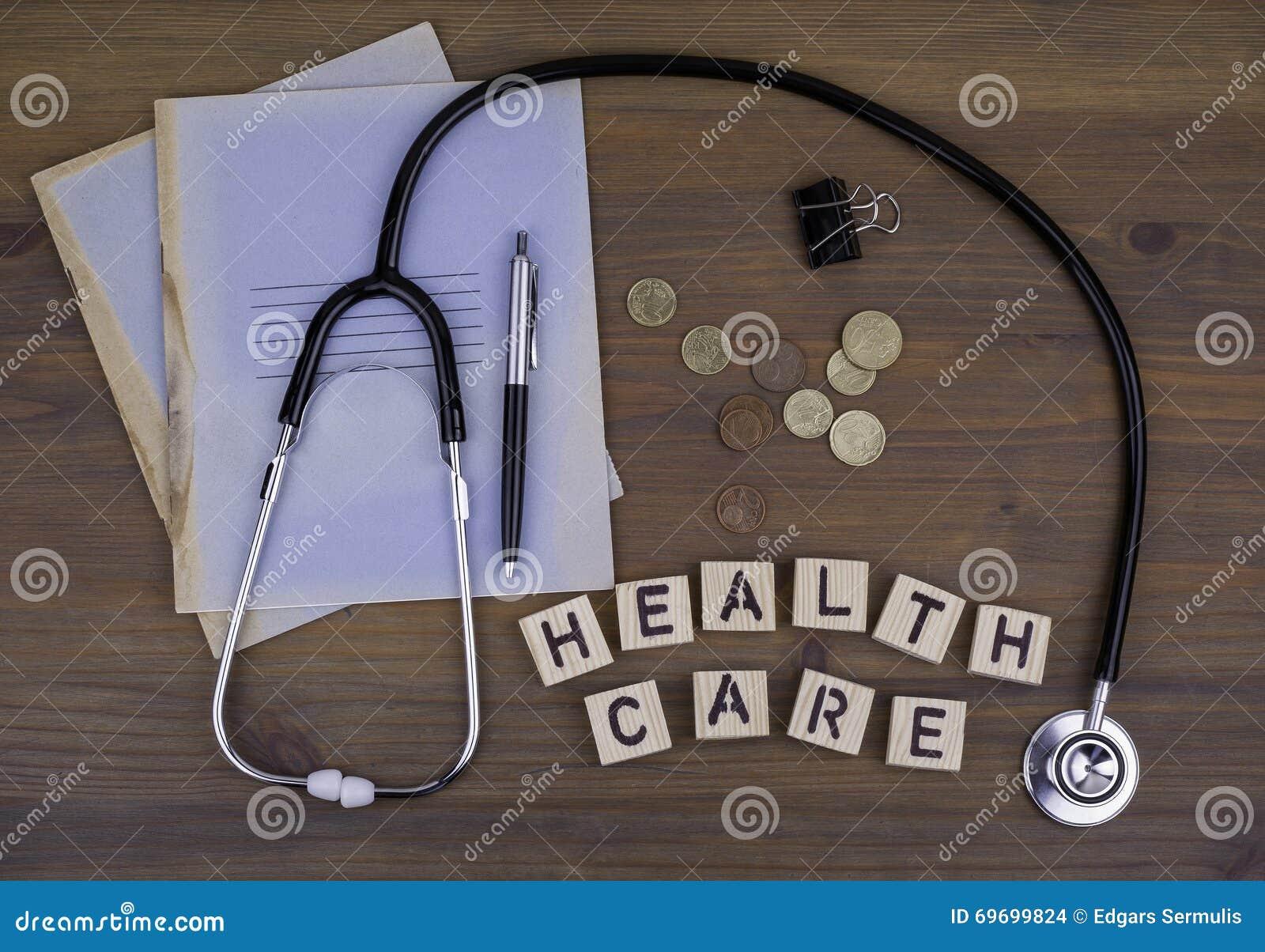 Stetoskop, pieniądze, pióro z notatnikiem i tekst: Opieka zdrowotna