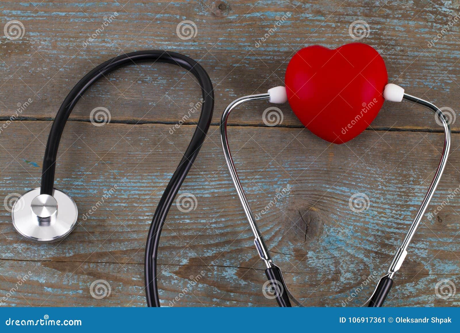 Stetoskop z czerwonym sercem na drewnianym tle