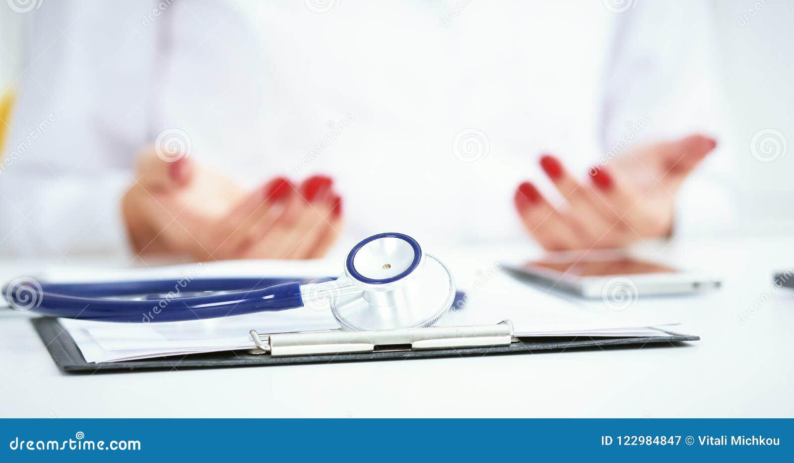 Stetoskopet den medicinska receptformen ligger mot bakgrunden av en doktor och en patient som diskuterar vård- examen