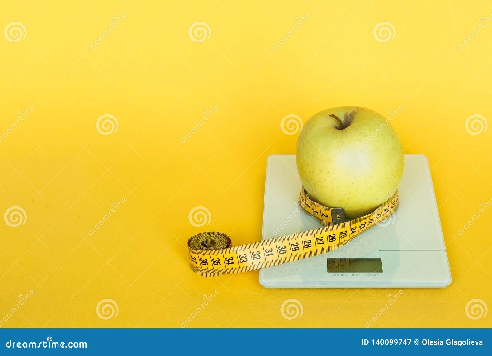 Stia il concetto a dieta Mele e scale della cucina del piano d appoggio e linea di misurazione del nastro su fondo giallo
