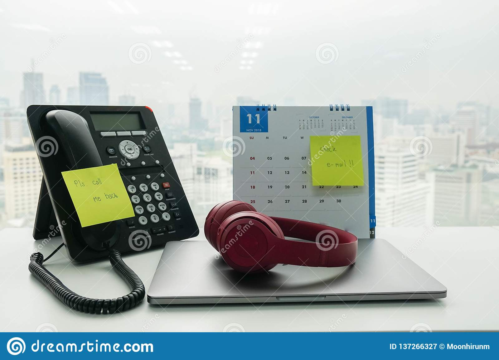 Stick note call back message and check e-mail on IP phone and November calendar for employee reminder with notebook computer an