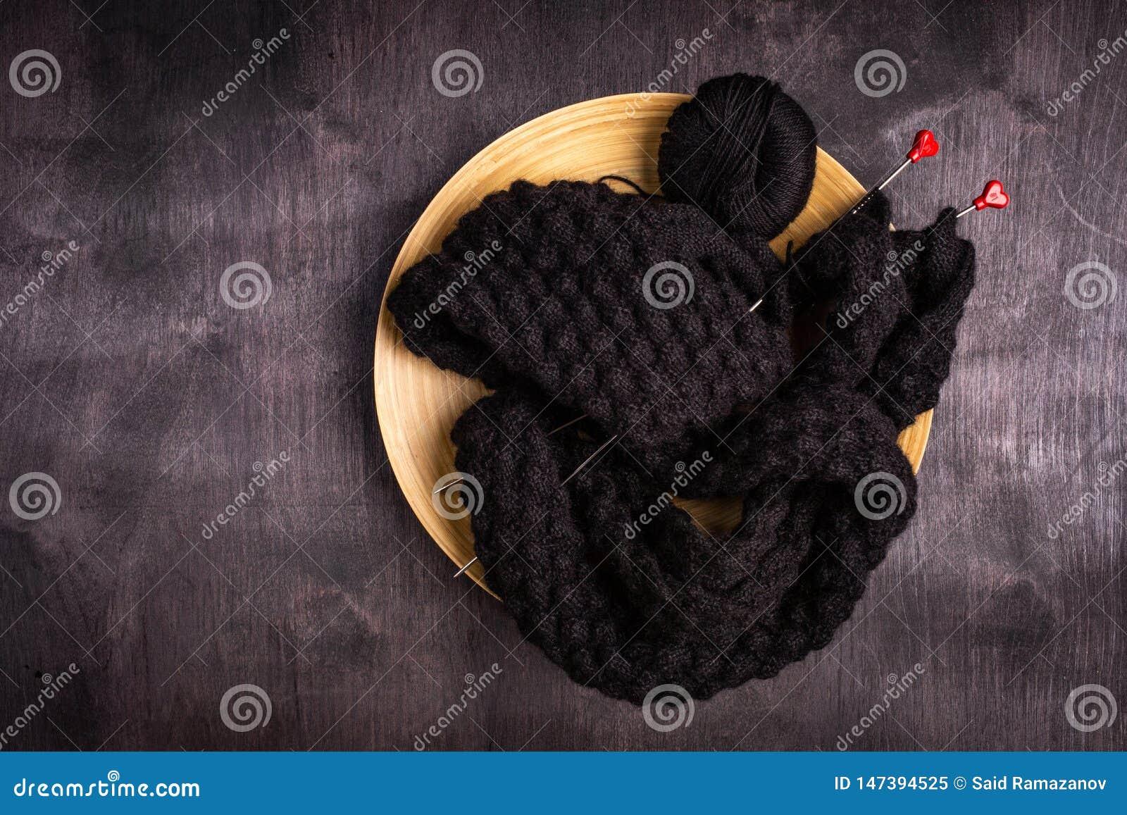 Sticka av svarta trådar i en platta på en svart och en grå träbakgrund