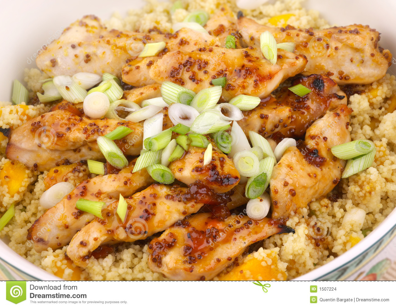 Sticky Chicken with mango couscous, garnished with spring onions and a ...
