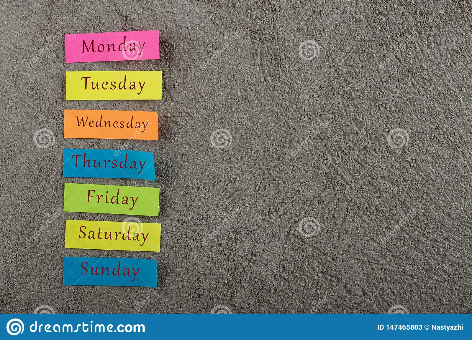sticky note with days of week on grey cement background. Monday, Tuesday, Wednesday, Thursday, Friday, Saturday, and Sunday