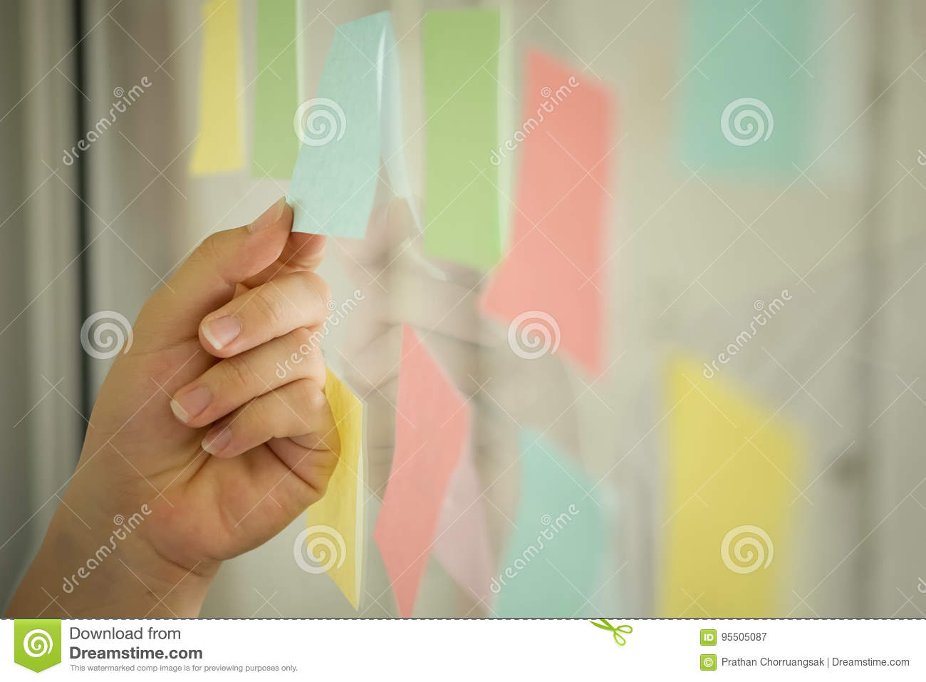 Sticky note paper on window,business man use post it note.