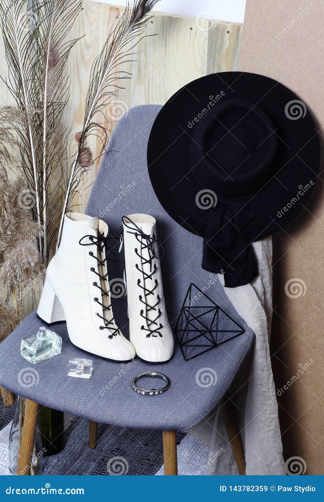 Stiefel der weißen Frauen der Mode und schwarzer Hut auf dem Stuhl