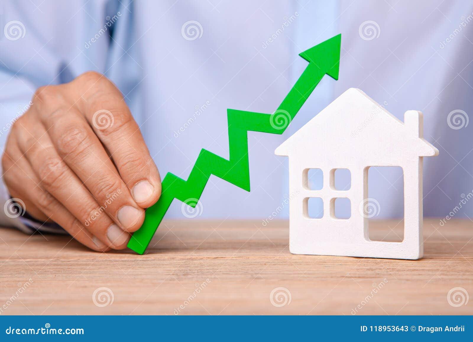 Stigande huspriser Mannen rymmer den gröna pilen upp i hans hand och hus