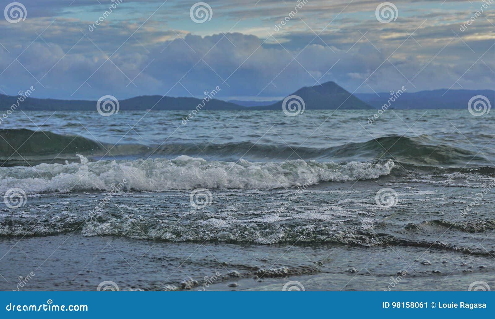 Stigande vatten på Taal sjön med den Taal vulkan som bakgrunden