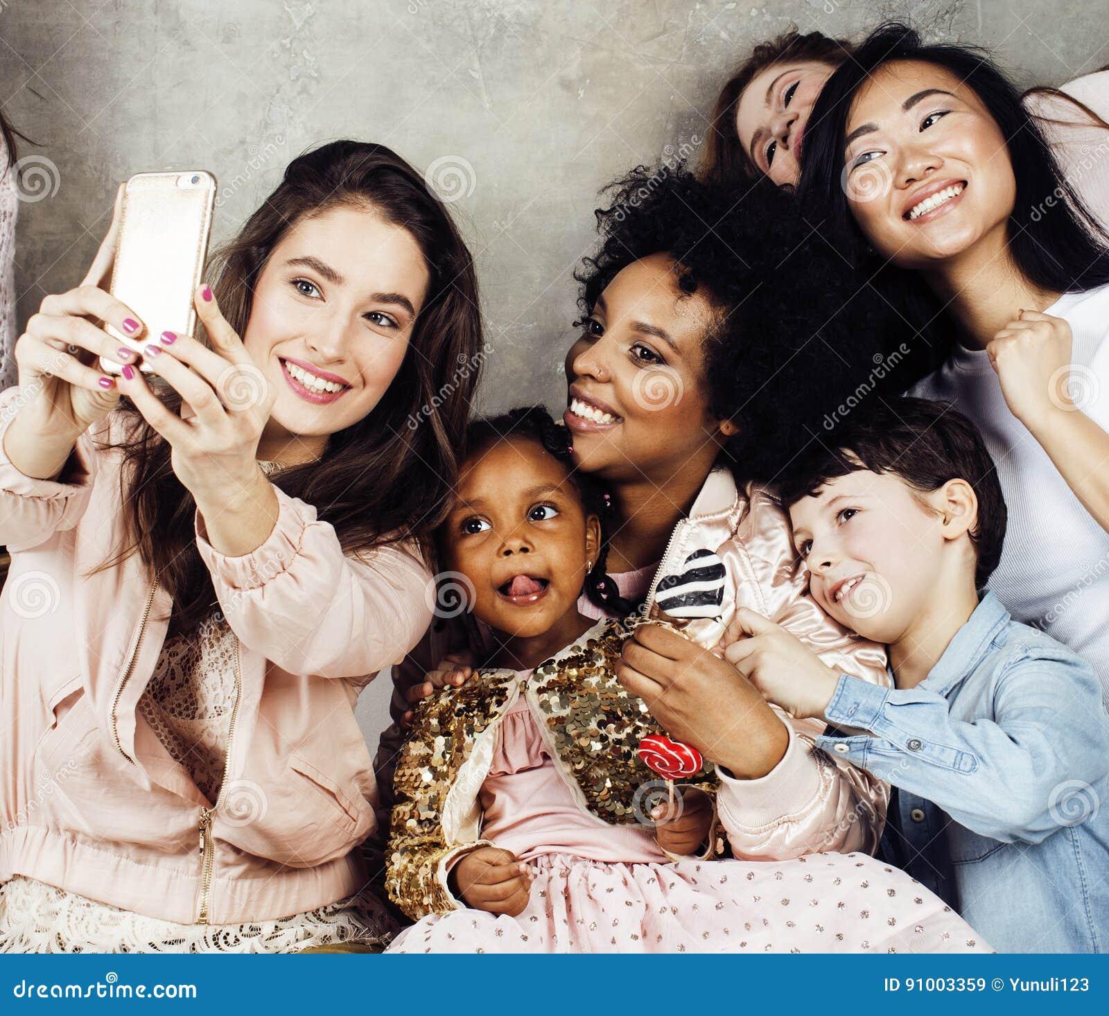 Stile di vita e concetto della gente: giovane donna graziosa di nazioni di diversità con differenti bambini di età che celebrano