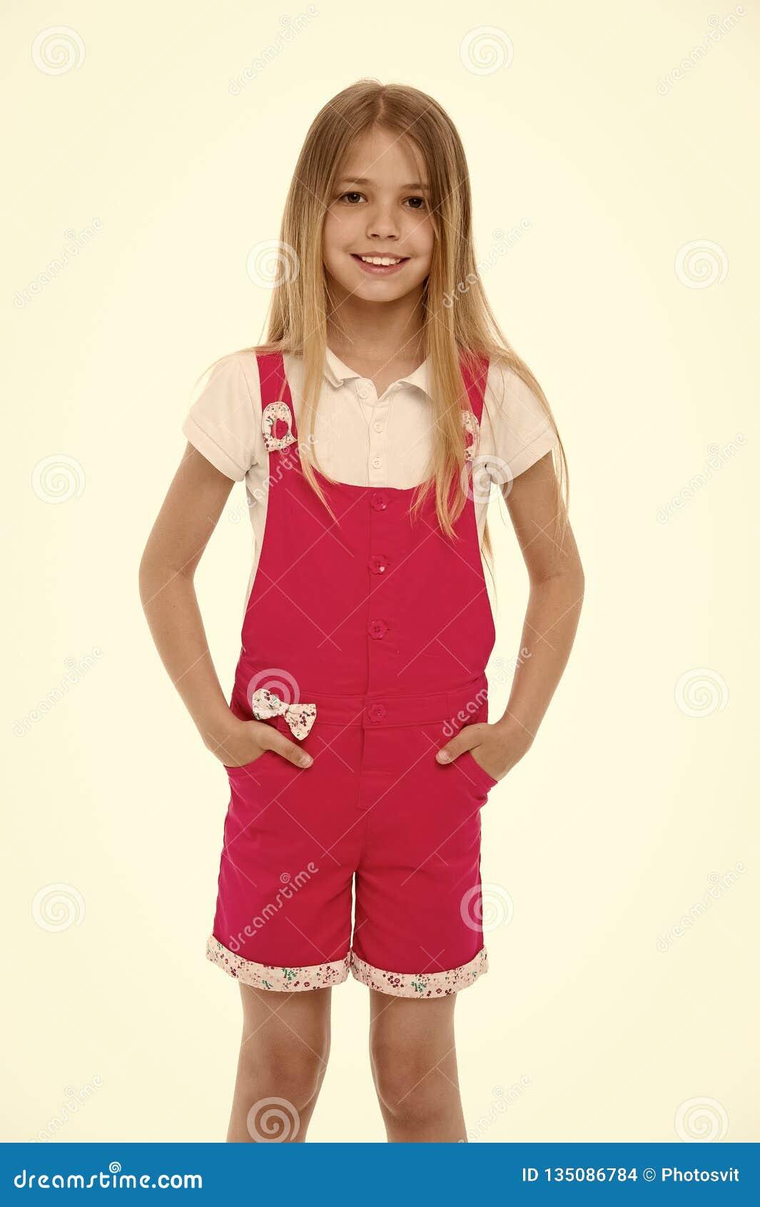 Stile e tendenza di modo Piccolo sorriso della ragazza in tuta rosa isolata su bianco Bambino che sorride con i capelli biondi lu