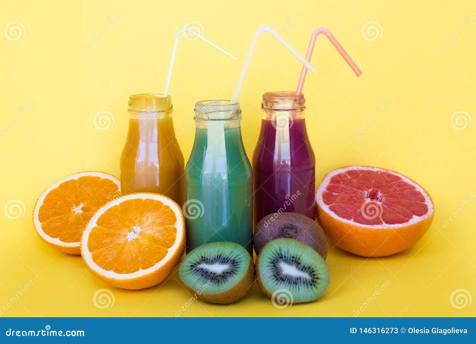 Stile naturale dell alimento biologico Succhi differenti in bottiglie con gli ingredienti sulla tavola gialla