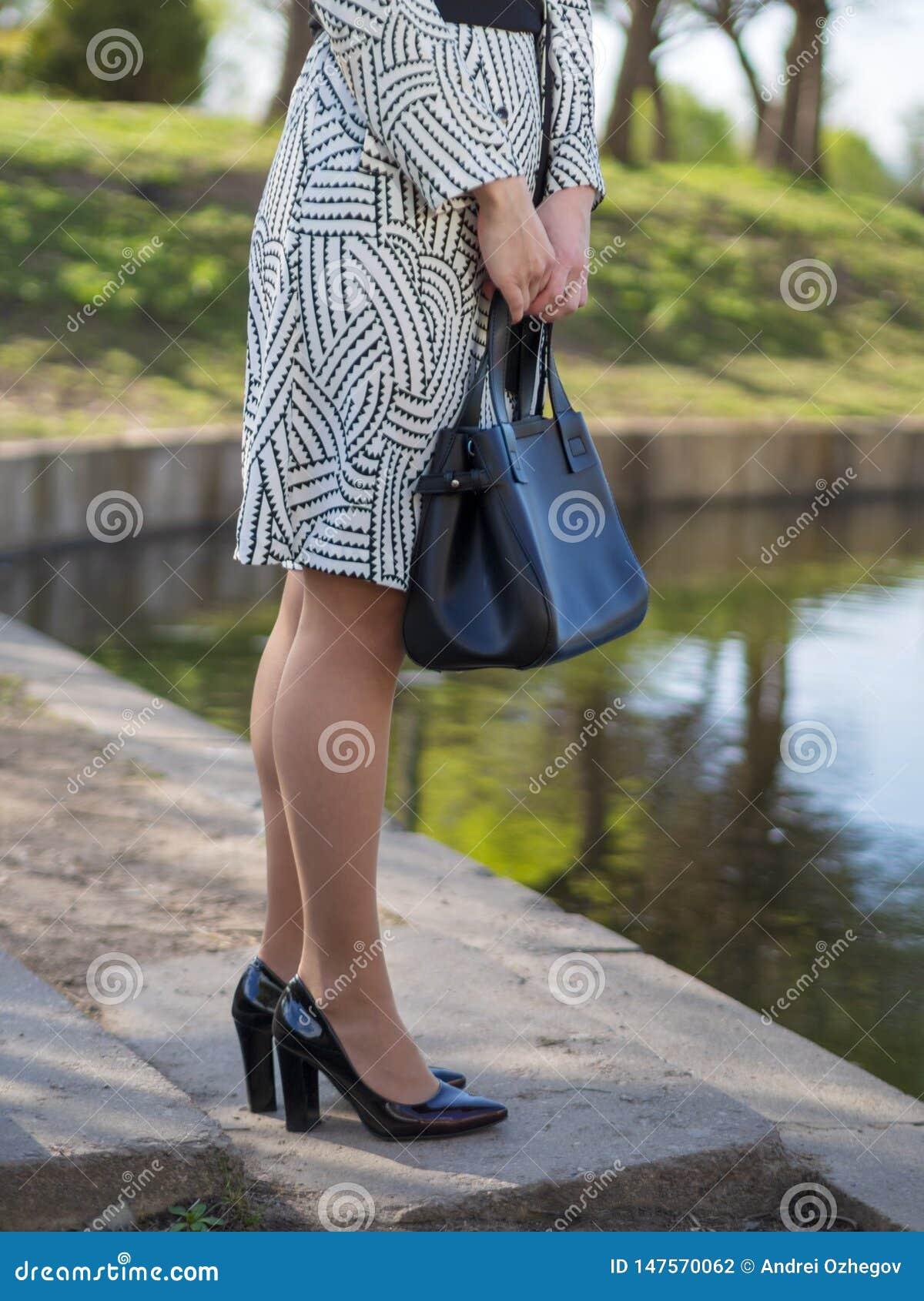 Stilfull europeisk ung kvinna i en regnrock,