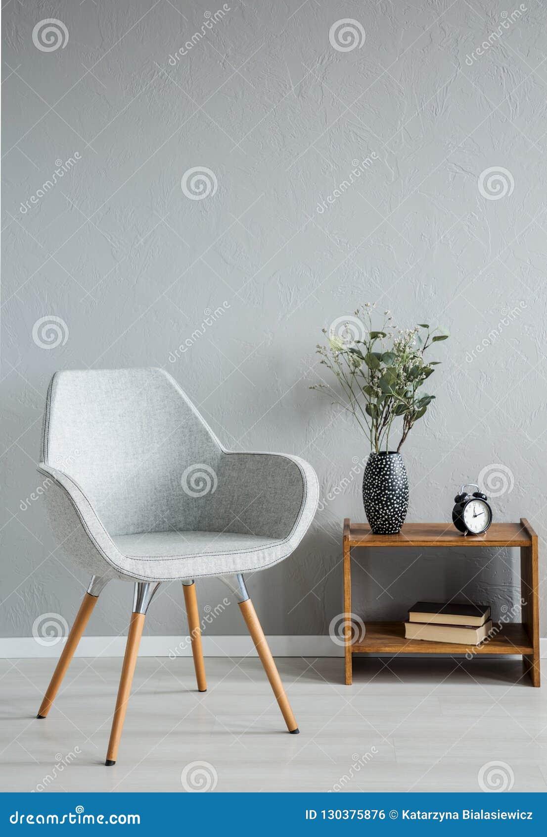 Stilfull grå stol bredvid kabinettet med vasen och blommor i den moderna kontorsinre, verkligt foto