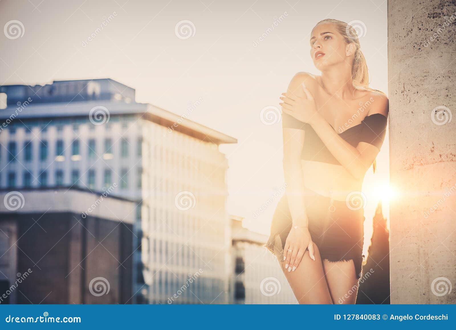 Stilfull kvinna med stads- solnedgång bakom Tillfällig kläder, blont hår och sinnlig inställning