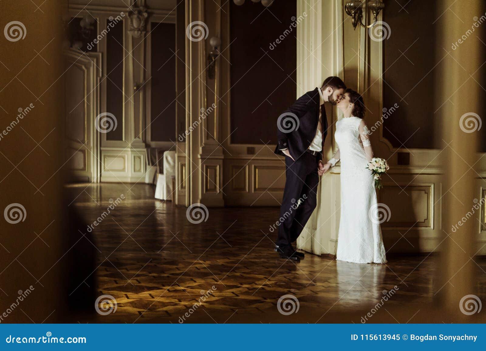 Stilfull lyxig brud och stilig elegant brudgum som kysser på bet