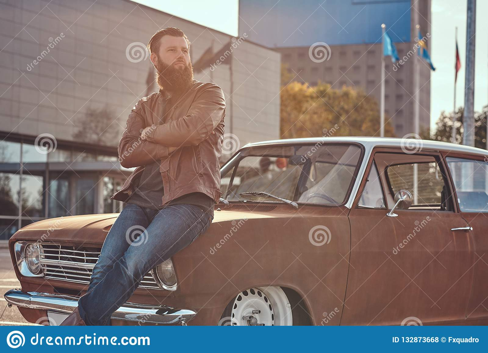 Stilfull man som lutar på den stämda retro bilen i staden som parkerar nära skyskrapa på den ljusa solnedgången