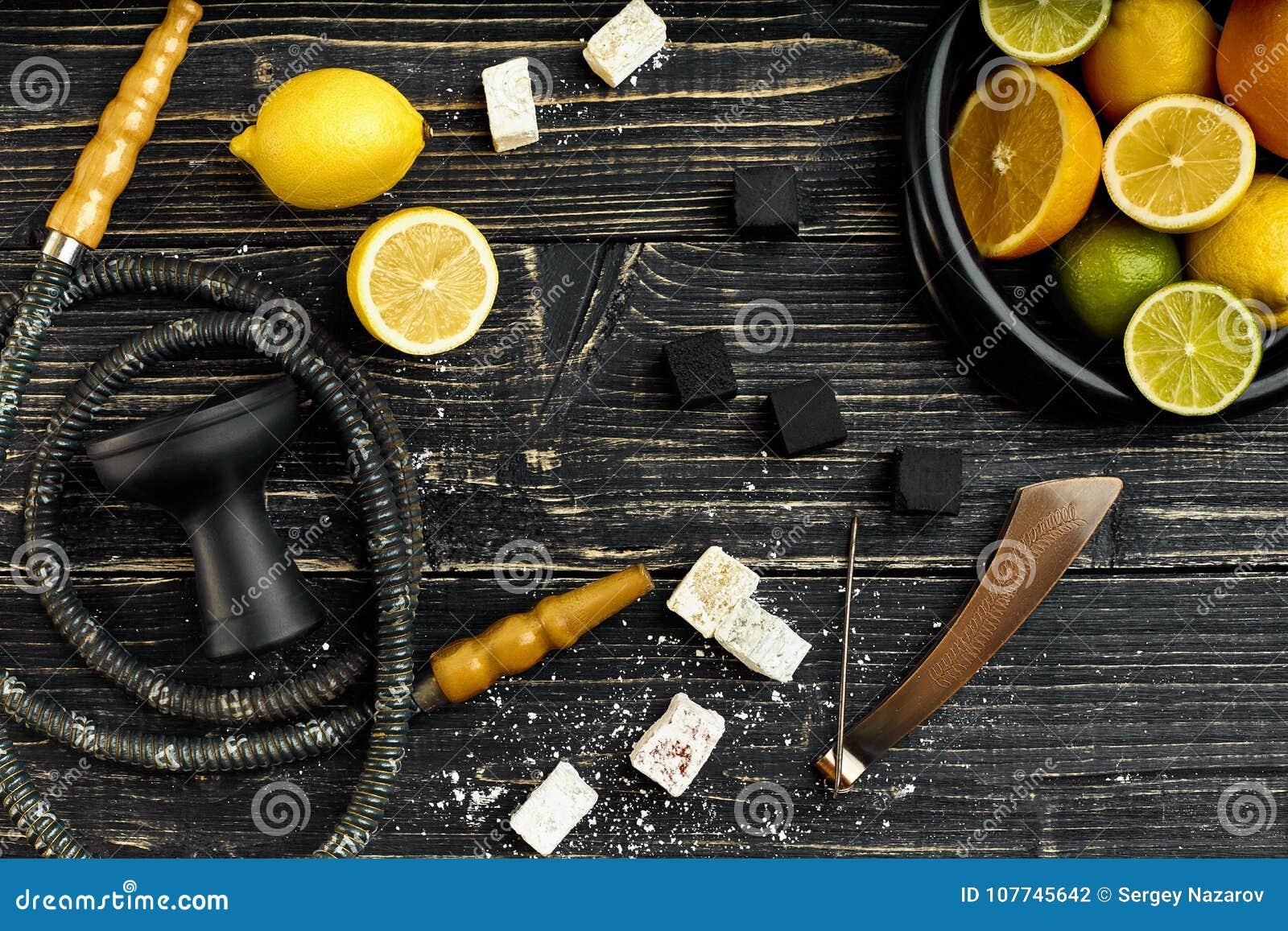 Stilfull röka vattenpipa och korg med citronen, limefrukt och apelsinen på