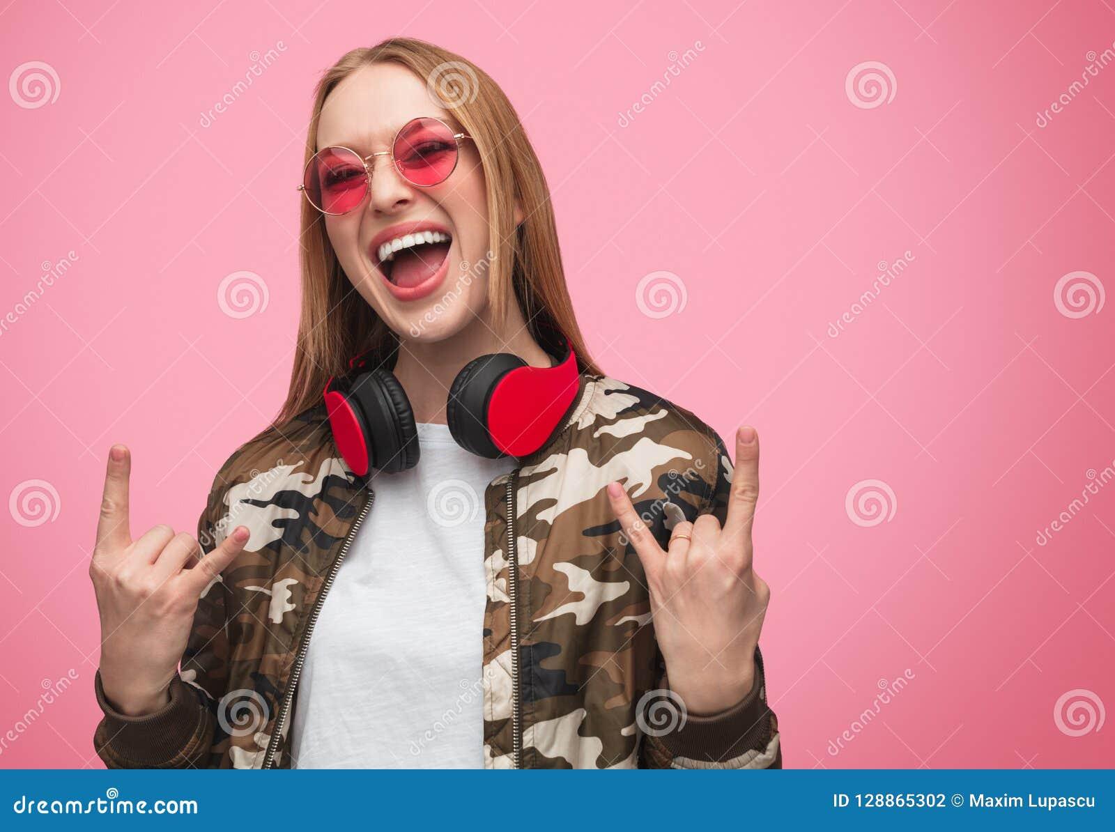 Stilfull rebellisk kvinna i solglasögon och hörlurar
